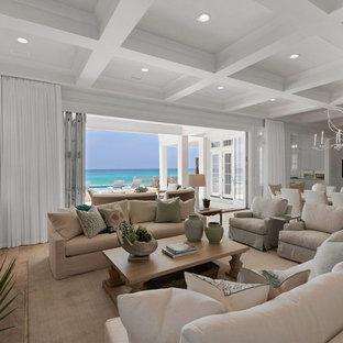 マイアミの巨大なビーチスタイルのおしゃれなLDK (白い壁、淡色無垢フローリング、標準型暖炉、タイルの暖炉まわり、壁掛け型テレビ) の写真