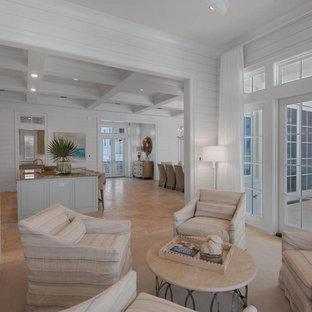 Example of a huge coastal travertine floor living room design in Miami with white walls, a standard fireplace and a tile fireplace
