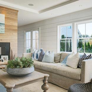 Esempio di un soggiorno stile marinaro aperto con pareti bianche, parquet chiaro, camino bifacciale e nessuna TV