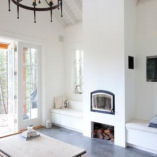 Exemple d'un salon bord de mer avec un mur blanc et une cheminée standard.