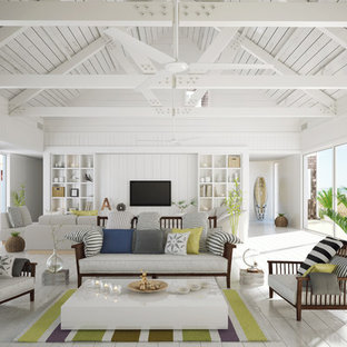 Offenes Maritimes Wohnzimmer mit weißer Wandfarbe, gebeiztem Holzboden und Wand-TV in San Diego