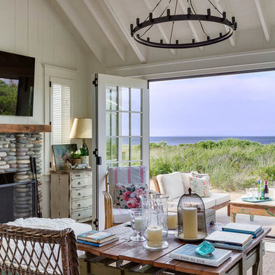 Small beach style open concept light wood floor living room photo in Other with white walls, a standard fireplace, a stone fireplace and a wall-mounted tv