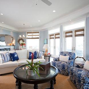 Esempio di un grande soggiorno stile marino aperto con pareti blu, parquet scuro, camino classico, cornice del camino in pietra e TV a parete