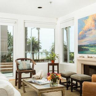 ロサンゼルスの大きいビーチスタイルのおしゃれなLDK (白い壁、カーペット敷き、標準型暖炉、漆喰の暖炉まわり、テレビなし、ベージュの床) の写真