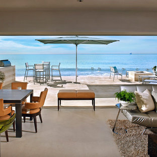 Inspiration for a large beach style open concept concrete floor living room remodel in Orange County with beige walls