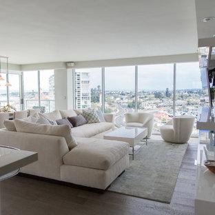 Foto de salón abierto, moderno, grande, sin chimenea, con suelo de madera clara, paredes blancas y televisor colgado en la pared