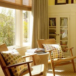 サンフランシスコの中サイズのトランジショナルスタイルのおしゃれな独立型リビング (黄色い壁、淡色無垢フローリング、標準型暖炉、木材の暖炉まわり) の写真