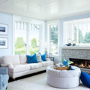 バンクーバーの中サイズのビーチスタイルのおしゃれなLDK (青い壁、濃色無垢フローリング、横長型暖炉、石材の暖炉まわり、テレビなし) の写真