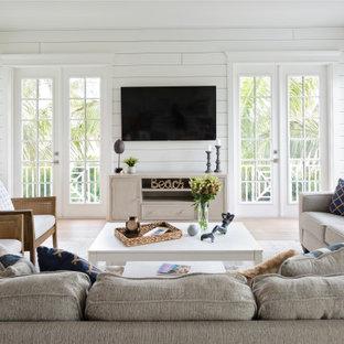 タンパの広いビーチスタイルのおしゃれなLDK (白い壁、淡色無垢フローリング、壁掛け型テレビ、ベージュの床、塗装板張りの壁) の写真