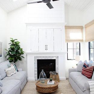 Immagine di un soggiorno stile marinaro aperto con sala formale, pareti bianche, camino classico, TV nascosta e pavimento grigio