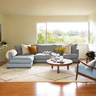 シアトルのミッドセンチュリースタイルのおしゃれなリビング (白い壁、無垢フローリング、標準型暖炉、レンガの暖炉まわり、テレビなし、オレンジの床) の写真