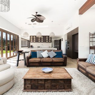 This is an example of a mediterranean open concept living room in Other with white walls, medium hardwood floors, brown floor and vaulted.