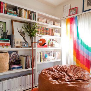 Ejemplo de biblioteca en casa bohemia con paredes blancas