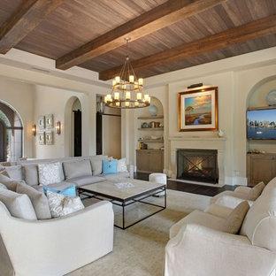 マイアミの広い地中海スタイルのおしゃれなLDK (フォーマル、ベージュの壁、濃色無垢フローリング、標準型暖炉、石材の暖炉まわり、テレビなし、グレーの床) の写真