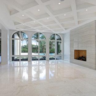 マイアミの広い地中海スタイルのおしゃれなLDK (フォーマル、グレーの壁、大理石の床、標準型暖炉、石材の暖炉まわり、テレビなし) の写真