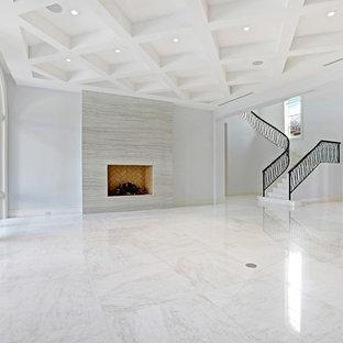 Esempio di un ampio soggiorno mediterraneo aperto con sala formale, pareti bianche, pavimento in marmo, camino classico, cornice del camino piastrellata e nessuna TV