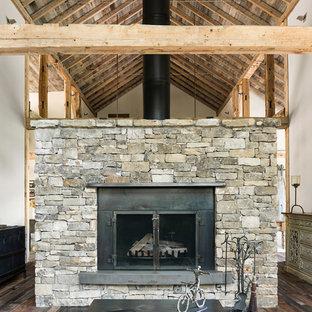 Modelo de salón abierto, rústico, pequeño, sin televisor, con paredes blancas, suelo de madera oscura, chimenea de doble cara, marco de chimenea de piedra y suelo marrón
