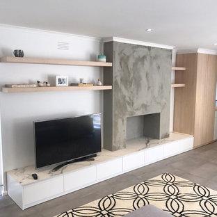 Immagine di un soggiorno minimalista di medie dimensioni e aperto con sala formale, pareti bianche, pavimento in ardesia, stufa a legna, cornice del camino in cemento, TV autoportante e pavimento grigio