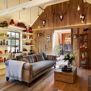 Modelo de salón abierto, rural, de tamaño medio, con paredes multicolor, suelo de madera en tonos medios y suelo marrón