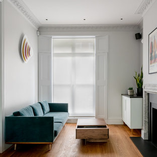 This is an example of a contemporary formal enclosed living room in London with white walls, medium hardwood flooring, a standard fireplace and no tv.