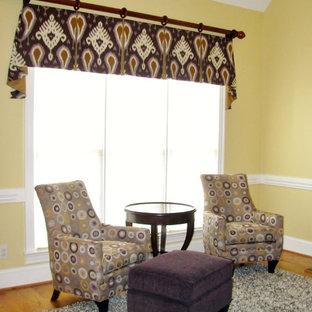 ローリーの中くらいのトランジショナルスタイルのおしゃれなLDK (黄色い壁、淡色無垢フローリング、標準型暖炉、木材の暖炉まわり、壁掛け型テレビ) の写真