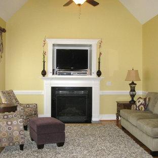 ローリーの中サイズのトランジショナルスタイルのおしゃれなLDK (黄色い壁、淡色無垢フローリング、標準型暖炉、木材の暖炉まわり、埋込式メディアウォール) の写真