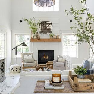 Esempio di un soggiorno country di medie dimensioni e aperto con pareti bianche, pavimento in legno verniciato, cornice del camino in legno, pavimento bianco e camino classico