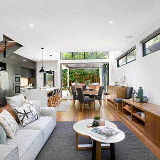 Design ideas for a contemporary open concept living room in Sydney with white walls, medium hardwood floors, no fireplace, a wall-mounted tv and brown floor.