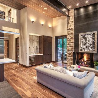 Modelo de salón con barra de bar abierto, rústico, grande, con suelo de madera en tonos medios, chimenea tradicional, marco de chimenea de metal, suelo marrón y paredes beige