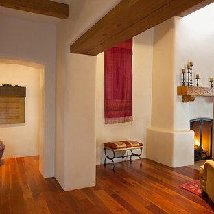 Exemple d'un grand salon sud-ouest américain ouvert avec un mur beige, un sol en bois brun, une cheminée standard, un manteau de cheminée en plâtre, une salle de réception et aucun téléviseur.
