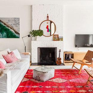 Imagen de salón para visitas ecléctico con paredes blancas, suelo de madera clara, chimenea tradicional, marco de chimenea de ladrillo, televisor colgado en la pared y suelo marrón