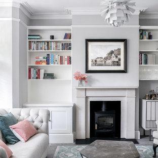 Exempel på ett klassiskt vardagsrum, med grå väggar, mörkt trägolv, en öppen vedspis och brunt golv