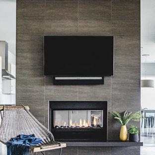 Example of a mid-sized trendy open concept concrete floor living room design in Austin with gray walls, a two-sided fireplace, a wall-mounted tv and a tile fireplace