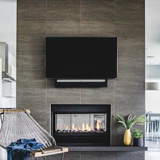 Foto di un soggiorno design di medie dimensioni e aperto con pareti grigie, pavimento in cemento, camino bifacciale, TV a parete e cornice del camino piastrellata