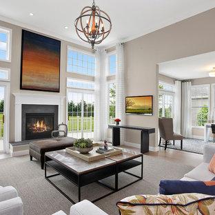 Diseño de salón para visitas abierto, tradicional renovado, con paredes grises, suelo de madera oscura, chimenea tradicional, marco de chimenea de hormigón y televisor colgado en la pared