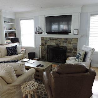 広いビーチスタイルのおしゃれなLDK (白い壁、淡色無垢フローリング、標準型暖炉、石材の暖炉まわり、壁掛け型テレビ、オレンジの床、ライブラリー) の写真