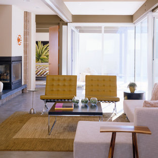 Inspiration for a modern concrete floor living room remodel in New Orleans with beige walls and a corner fireplace