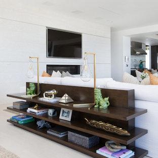 Esempio di un ampio soggiorno design aperto con sala formale, pareti bianche, pavimento in pietra calcarea, camino bifacciale, cornice del camino piastrellata e TV a parete
