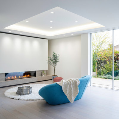 Living room - mid-sized modern open concept light wood floor and beige floor living room idea in Los Angeles with a ribbon fireplace, a plaster fireplace and white walls