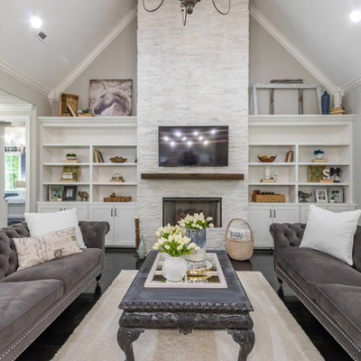 Example of a large transitional formal and open concept dark wood floor and brown floor living room design in San Francisco with gray walls, a standard fireplace, a stone fireplace and a wall-mounted tv