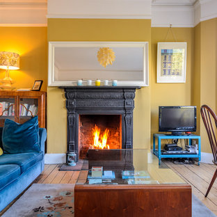 Design ideas for an eclectic living room in Belfast with yellow walls, medium hardwood floors, a standard fireplace and a freestanding tv.