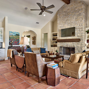 Large elegant open concept terra-cotta floor living room photo in Austin with beige walls, a standard fireplace, a stone fireplace and a wall-mounted tv