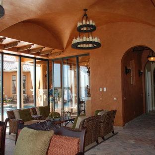 Idee per un soggiorno mediterraneo di medie dimensioni e aperto con sala formale, pareti arancioni, pavimento in mattoni e nessuna TV