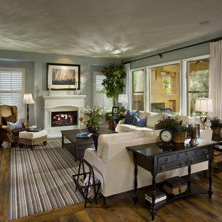 Aménagement d'un grand salon classique ouvert avec une salle de réception, un mur bleu, un sol en bois foncé, une cheminée standard, un manteau de cheminée en plâtre et un sol multicolore.