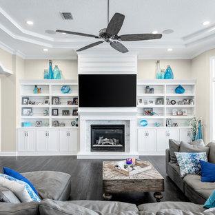 タンパの広いビーチスタイルのおしゃれなLDK (ベージュの壁、濃色無垢フローリング、標準型暖炉、石材の暖炉まわり、壁掛け型テレビ、グレーの床) の写真