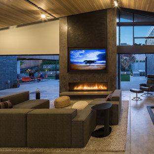シアトルの大きいミッドセンチュリースタイルのおしゃれなLDK (白い壁、コンクリートの床、標準型暖炉、漆喰の暖炉まわり、内蔵型テレビ) の写真