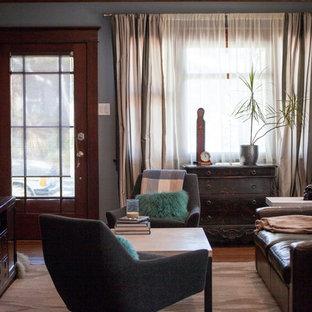 Foto di un piccolo soggiorno stile americano chiuso con pareti grigie, pavimento in legno massello medio e TV autoportante