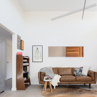 This is an example of a contemporary formal open concept living room in Wollongong with white walls and grey floor.