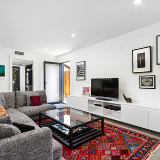 Design ideas for a contemporary enclosed living room in Wollongong with white walls, a freestanding tv and grey floor.