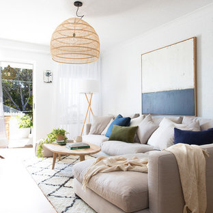 Inspiration for a beach style living room in Brisbane with white walls, medium hardwood floors and brown floor.